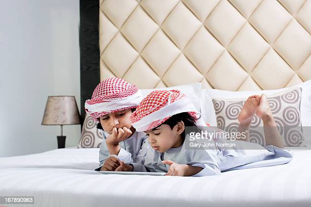 Two Arab boys in traditional dress lay on bed