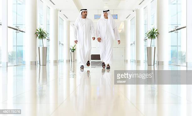 Two arab business men walking, talking, meeting