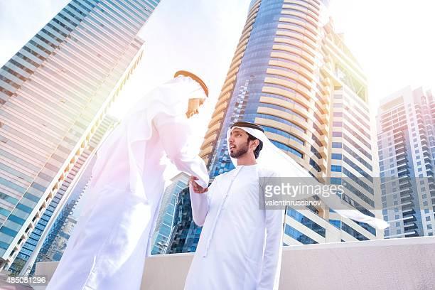 Two arab business people on the street handshake