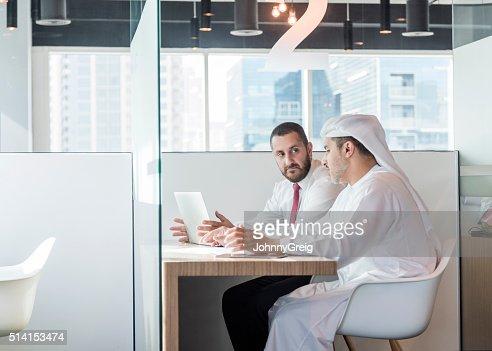 Two Arab businessmen in office cubicle, Dubai, UAE