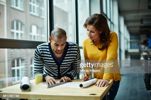 Two architects discussing project at high table : Stock Photo
