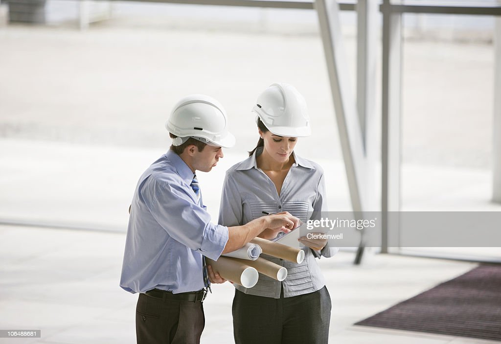 Two architects in discussion with blueprints at office : Stock Photo