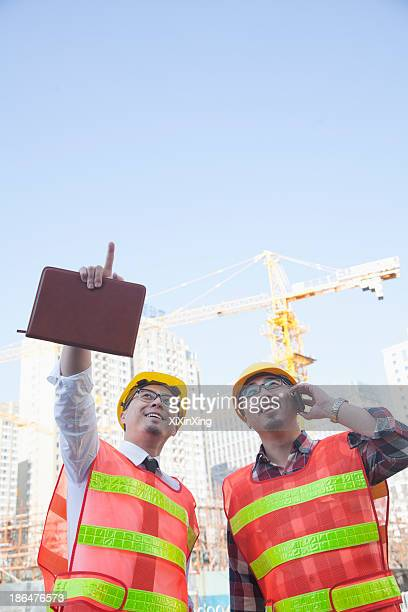 Two architects looking and pointing at construction site