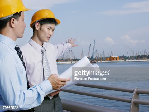 Two architects on site holding plans : Stock Photo
