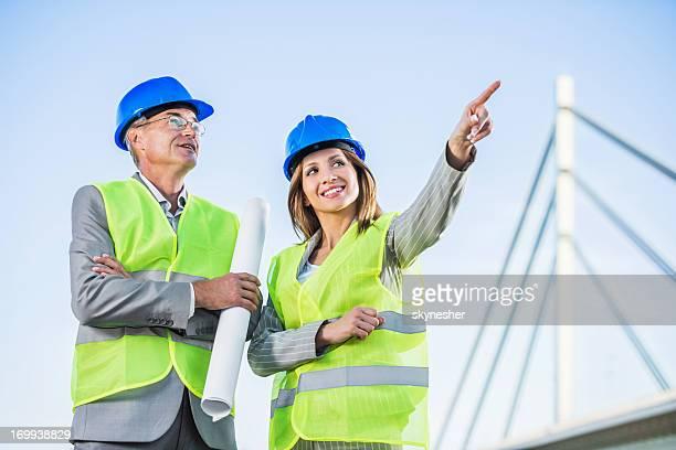 Deux architectes à l'extérieur contre le ciel.