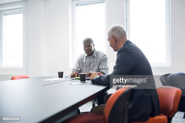 Two architects talking at table in office