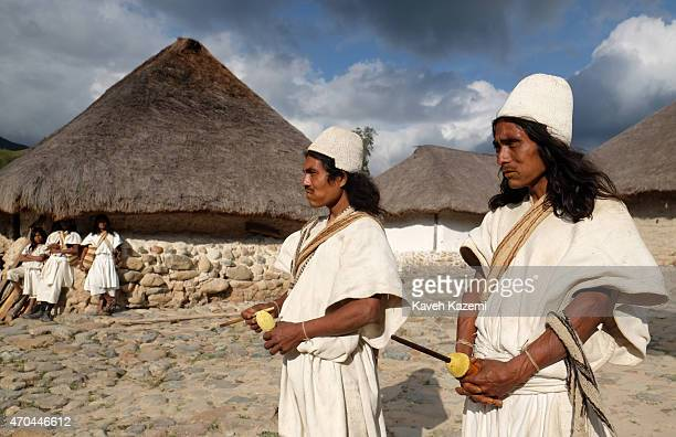 Two Arhuaco men dressed in white serapes tall coned hats with long black hair carrying stitched mochila handbags hold Poporos in their hands while...