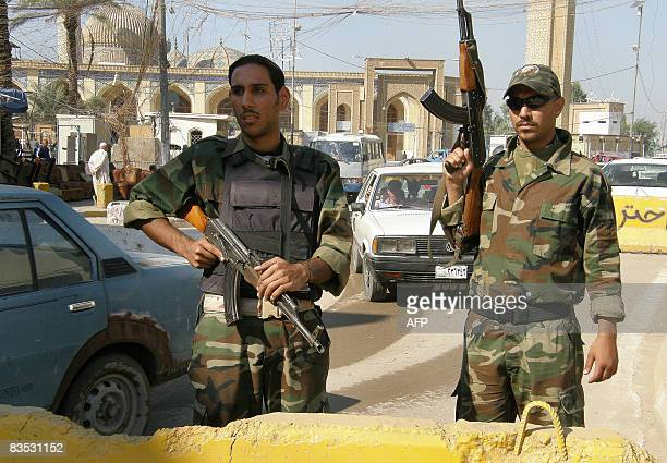 Two armed Iraqi militiamen members of the Sahwa militias former Sunni insurgents who have switched to backing the United States man a checkpoint in...