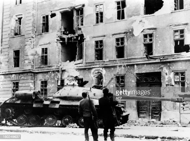 Two armed men look at a Soviet tank on November 04 1956 in front of the destroyed Killian garrison house in Budapest The Hungary uprising broke out...