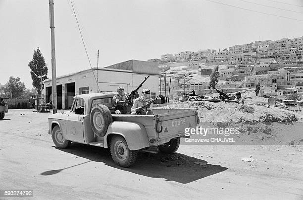 Two armed Palestinian Fedayeen soldiers of the Popular Front for the Liberation of Palestine ride in the back of a pickup in Amman Jordan