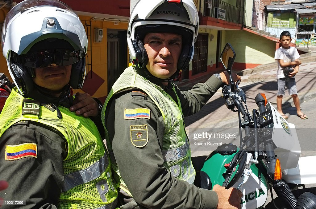 Two armed policemen on a motorbike patrol a small alley way on January 5, 2013 in Medellin, Colombia. The notorious slums of Medellin have gone through urban and educational projects to improve the quality of life for its residence.