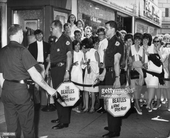Two armed Wells Fargo guards carry canisters with prints of director Richard Lester's film 'A Hard Day's Night' starring the rock group The Beatles...