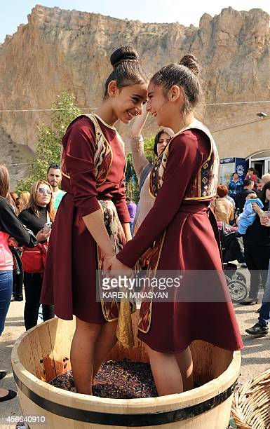 Two Armenian girls tramp grapes in order to make wine during a wine festival devoted to grapegathering in the village of Areni on October 4 2014 AFP...