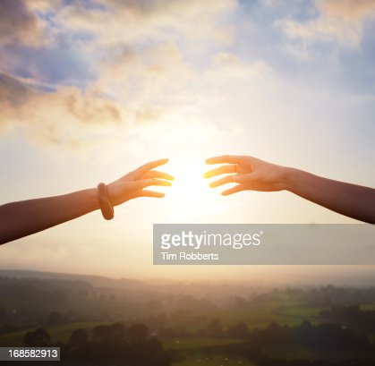 Two arms reaching together with sun.