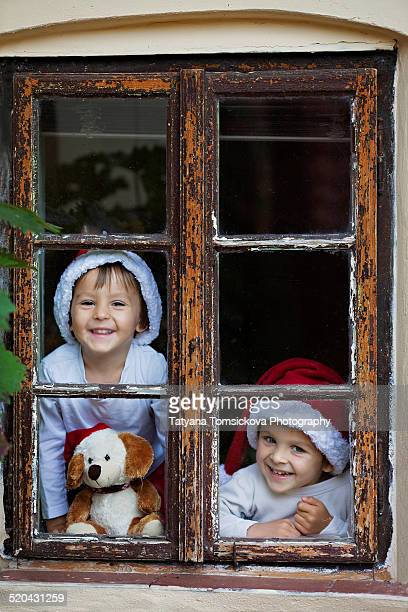 Two arodable boys, sitting on a window, smiling