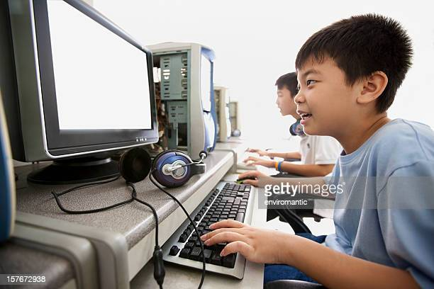 Two Asian boys in an internet cafe.