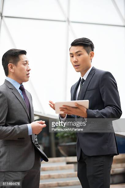 Two Asian Businessmen with Computer Tablet Having Serious Discussion Outdoors