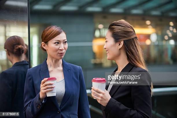 Two Asian Businesswomen Having Coffee Outside Office Building