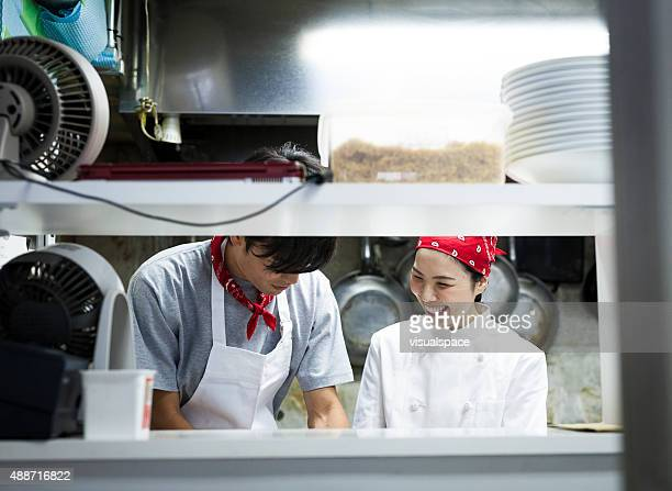 Two Asian Chefs Working in the Kitchen