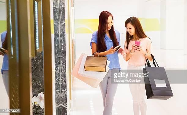 Dois amigos asiática Loja com telemóveis a mall