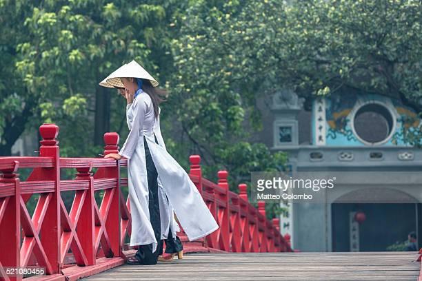 Two asian girl in Ao Dai dress on bridge, Vietnam