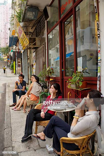Two Asian girls sitting outside of a cafe to enjoy their coffee on a street in the city of Hong Kong