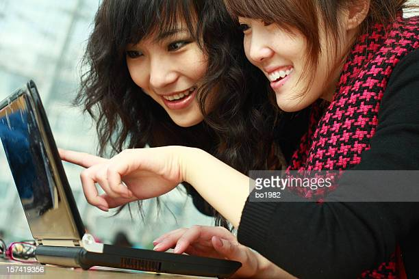 two asian students with their laptop