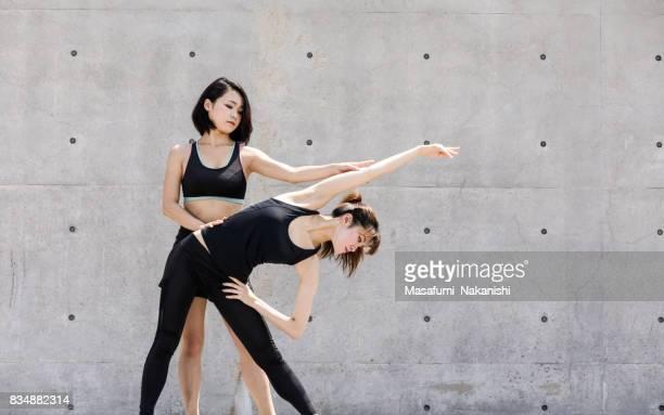 Two Asian women stretching outdoors