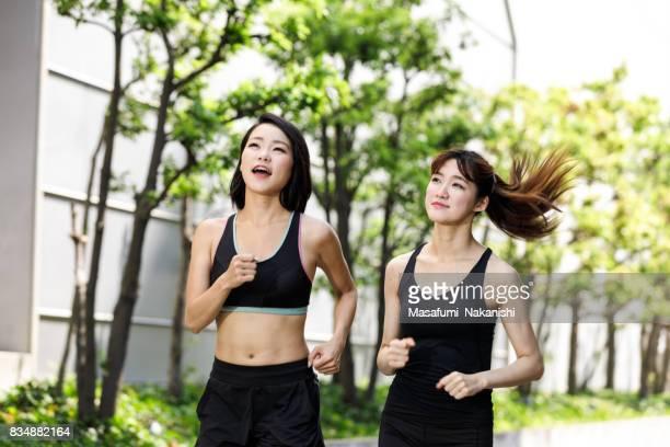 Two Asian women who enjoy jogging outdoors