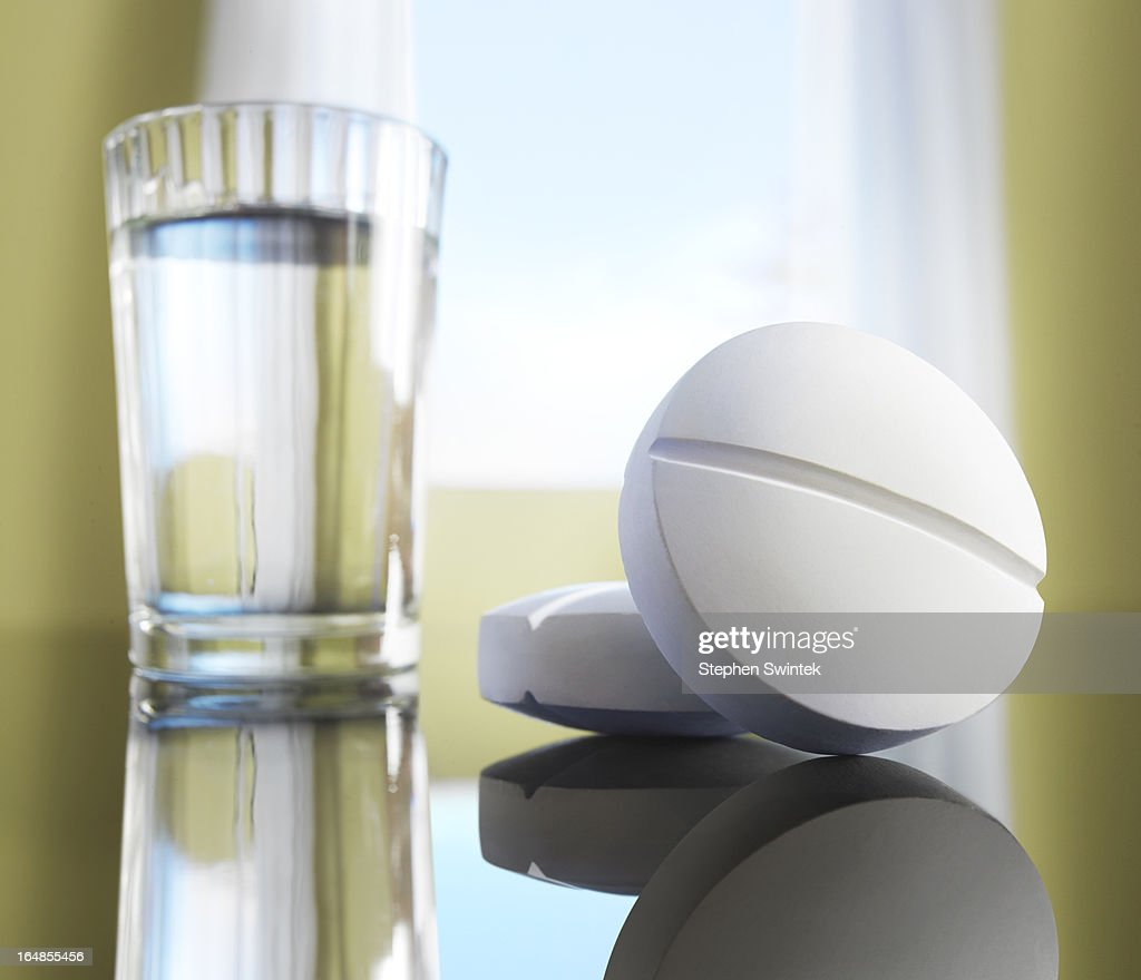 Two aspirins with a glass of water