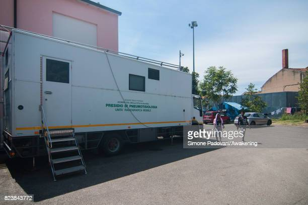 Two asylum seekers walk close to the mobile radiographic unit used to check asylum seekers health on their arrival and during their stay at the CARA...
