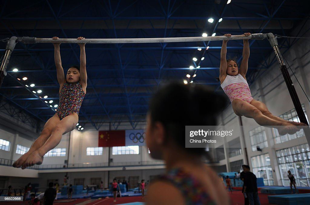 Two athletes attend a training session during the 2010 Training Camp For Country's Reserve Gymnastic Athletes at the Gymnastic Hall of Hubei Olympic...