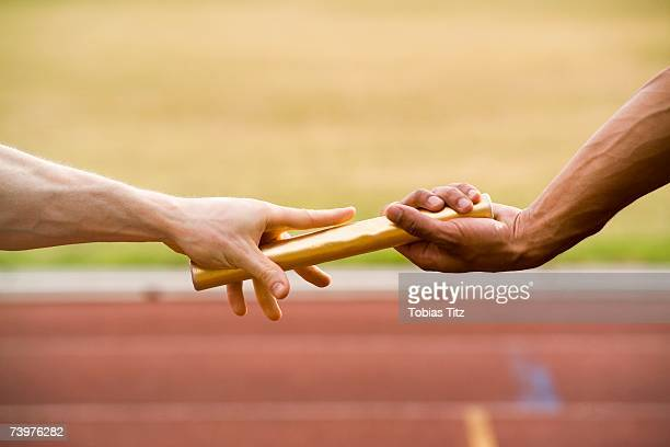 Two athletes exchanging a baton during a relay race