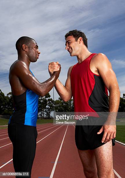 Two athletes shaking hands on running track