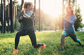 Two athletic female friends wearing jumpsuits doing lunges together training outdoors.