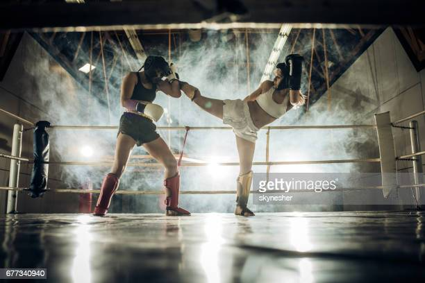 Two athletic women fighting on a kickboxing match in a gym.