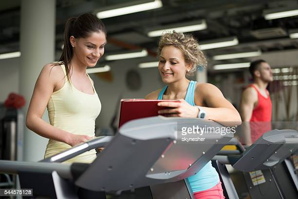 Two athletic women looking at exercise plan in a gym.