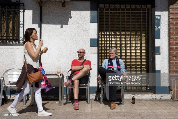 Two Atletico de Madrid fans look to a woman eating a sandwich before the La Liga match between Club Atletico de Madrid and Sevilla FC at Vicente...