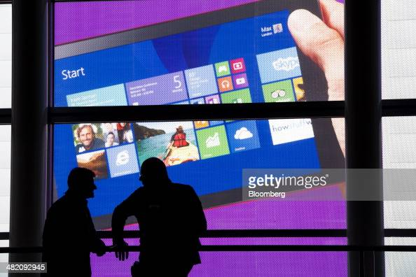 Two attendees are silhouetted against a Microsoft Corp poster at the Microsoft Developers Build Conference in San Francisco California US on...