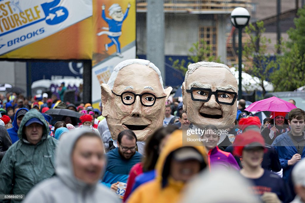Two attendees wearing large heads in the likeness of Warren Buffett, chairman and chief executive officer of Berkshire Hathaway Inc., right, and Charlie Munger, vice chairman of Berkshire Hathaway, run at the start of the 'Berkshire Hathaway Invest In Yourself 5K' race presented by Brooks Sports, Inc., a Berkshire company, on the sidelines the Berkshire Hathaway annual shareholders meeting in Omaha, Nebraska, U.S., on Sunday, May 1, 2016. Dozens of Berkshire Hathaway subsidiaries will be showing off their products as Chief Executive Officer Warren Buffett hosts the company's annual meeting. Photographer: Daniel Acker/Bloomberg via Getty Images