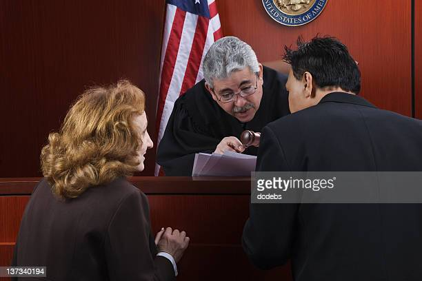 Two attorneys speaking with the judge in the courtroom