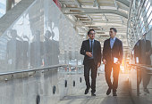 two attractive business man discussion and walking at outdoor on morning.