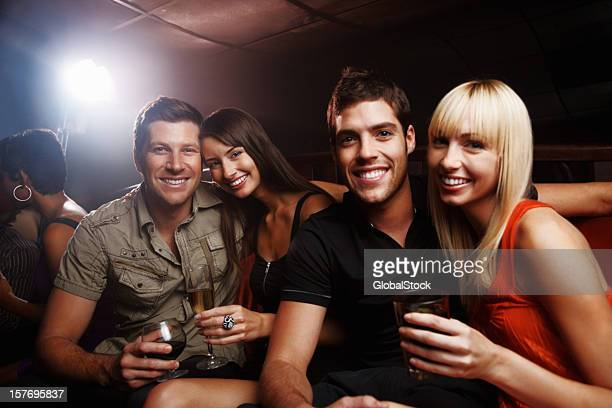 Two attractive couples with drinks having fun at night party