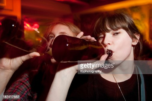 Two Attractive Young Women Drinking Beers at a Bar