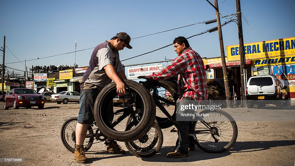 Two auto mechanics compare tires on June 17, 2013 in the Willet's Point neighborhood of the Queens borough of New York City. The Willet's Point Neighborhood, also known as the Iron Triangle, is situated directly next to Citi Field, where the Met's play baseball, and is known for both its car repair shops and lack of paved roads. The future of the neighborhood has been a contentious issue between residents and the city, as the city hopes to further develop the land despite protests from its residents.