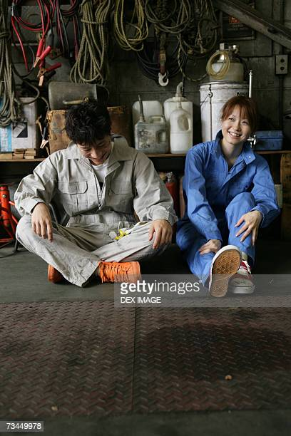 Two auto mechanics sitting in an auto repair shop and smiling