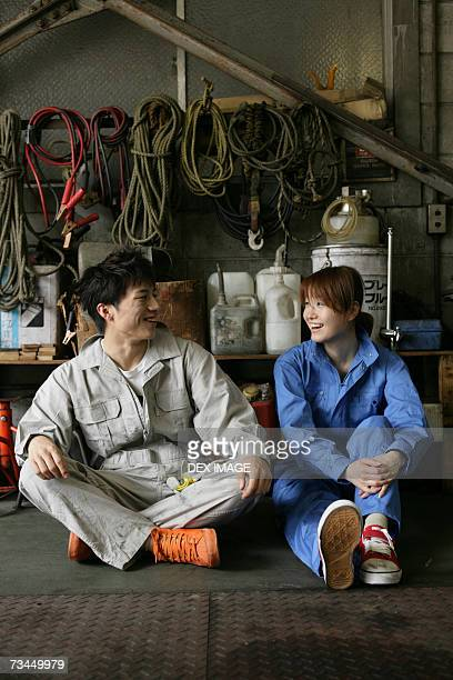 Two auto mechanics talking in an auto repair shop