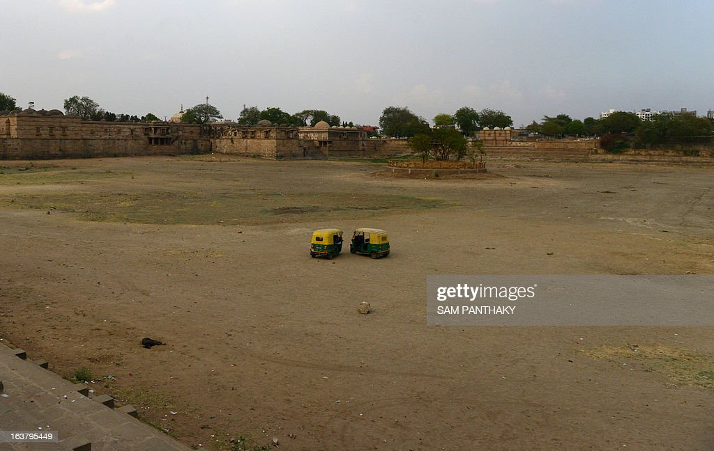 Two auto-rickshaws are parked as a dog sleeps on the dry bed of the Ahmad Sar Lake at Sarkhej Roza, the 15th century monument which houses the tomb of Saint Ahmed Khattu Baksh, spiritual counselor of Ahmedabad city's founder Ahmed Shah, southwest of Ahmedabad on March 16, 2013. Many districts of western Gujarat state, which received less monsoon rain than normal last year, are experiencing water scarcity. AFP PHOTO / Sam PANTHAKY