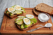 two sliced tasty avocado sandwiches with egg and spices on a wooden Board. Concept of Keto diet