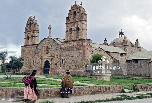 Two Aymara indigenous women walk in front of the stone church in Laja 35 km west of La Paz on February 23 2010 AFP PHOTO/ Aizar Raldes